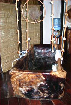 Azulik EcoTulum Resorts cottage interior with zapote log bathtub.