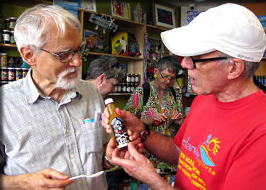 Two men discuss hot and spicy pepper sauces on a Bahamian food tasting tour around Old Nassau.