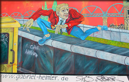 Mural of man escaping over the Berlin Wall, Berlin historic and contemporary street art.