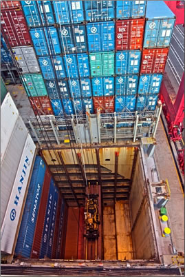 Containers stacked below and above deck: cargo ship travel around the world.