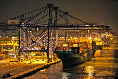 Shipping terminal night scene: freighter travel Pacific Ocean countries.