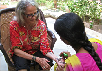 Henna painting on hand, women travel groups in India.