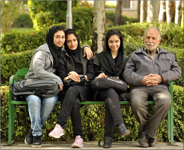 Three Iranian teens and their father sitting in the gardens of a palace park in Tehran.