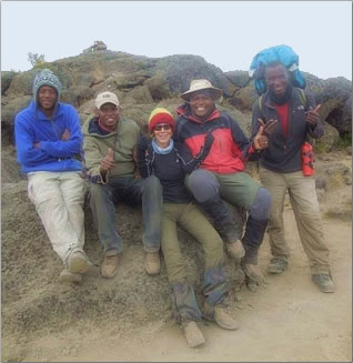 Article about senior woman trekking to the summit of Mt Kilimanjaro, seen here with her guides.