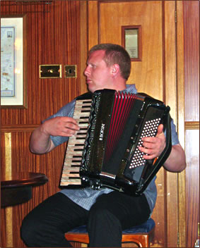 Captain of the Scottish Highlander luxury barge plays accordion for guests.