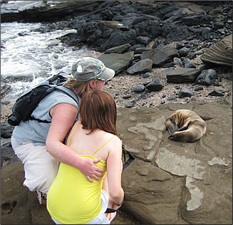 Ecoventura mother and daughter with baby sea lion, Galapagos Islands: family travel cruise holidays.