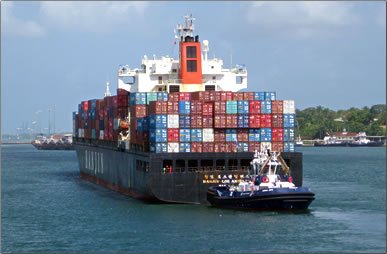Containership guided by tug through Panama Canal, Panama Canal 100th anniversary.