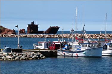 Shipwreck and fishing boats: Quebec's Les Îles de la Madeleine, Magdalen Islands.