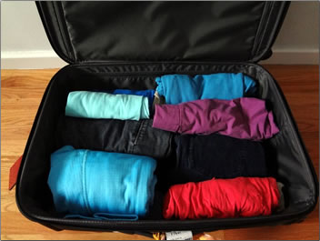 Open suitcase with clothes rolled, what to pack on vacation.