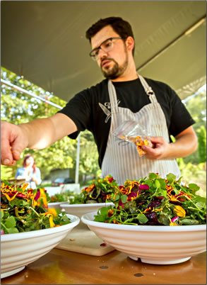 Chef Chris Whittaker of Forage Restaurant in Vancouver, BC decorates salads.