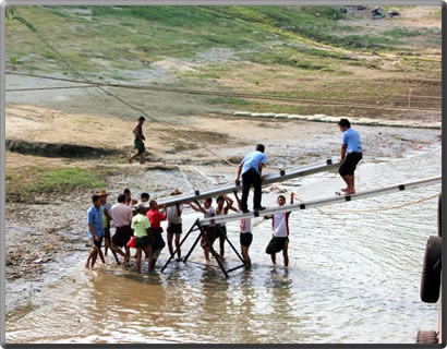 Building a footbridge gangaway from Irrawaddy River cruise ship to the muddy river bank.