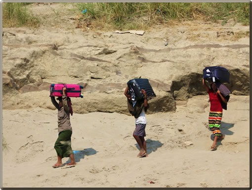 Women porters in Myanmar carry suitcases to river cruise ships on the Irrawaddy River.
