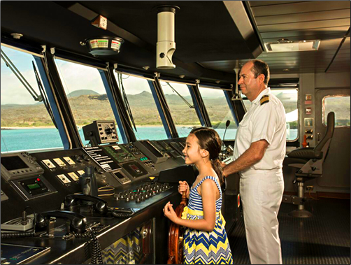 Children may visit the ship's bridge on the Santa Cruise II while exploring the Galapagos Islands. AdventureSmith Explorations