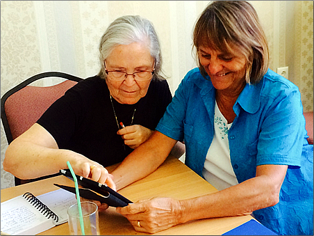 Lynn explores technology with an older woman during a community activity.